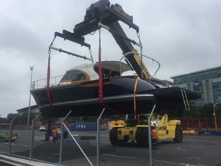 Yacht on crane lifted into water
